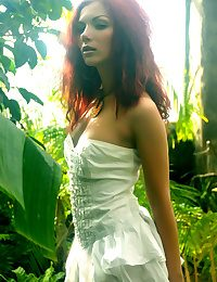 A redhead nymph slowly strips off her dainty dress, revealing a smooth fair complexion and gorgeous physique that stands out from the lush, green surroundings.