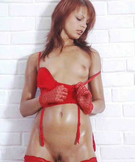 Luxurious red-haired with well-lubed figure posing in a mittens and crimson fishnets