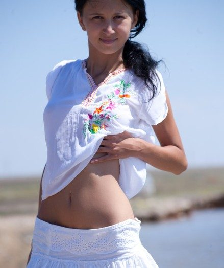 X black-haired nubile posing bottomless on the beach